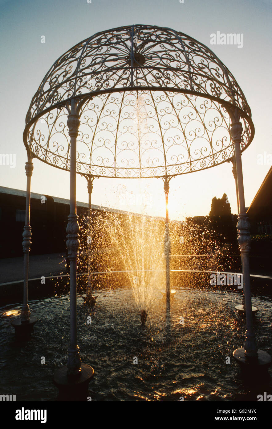 Backlit sunset view of decorative water fountain - Stock Image