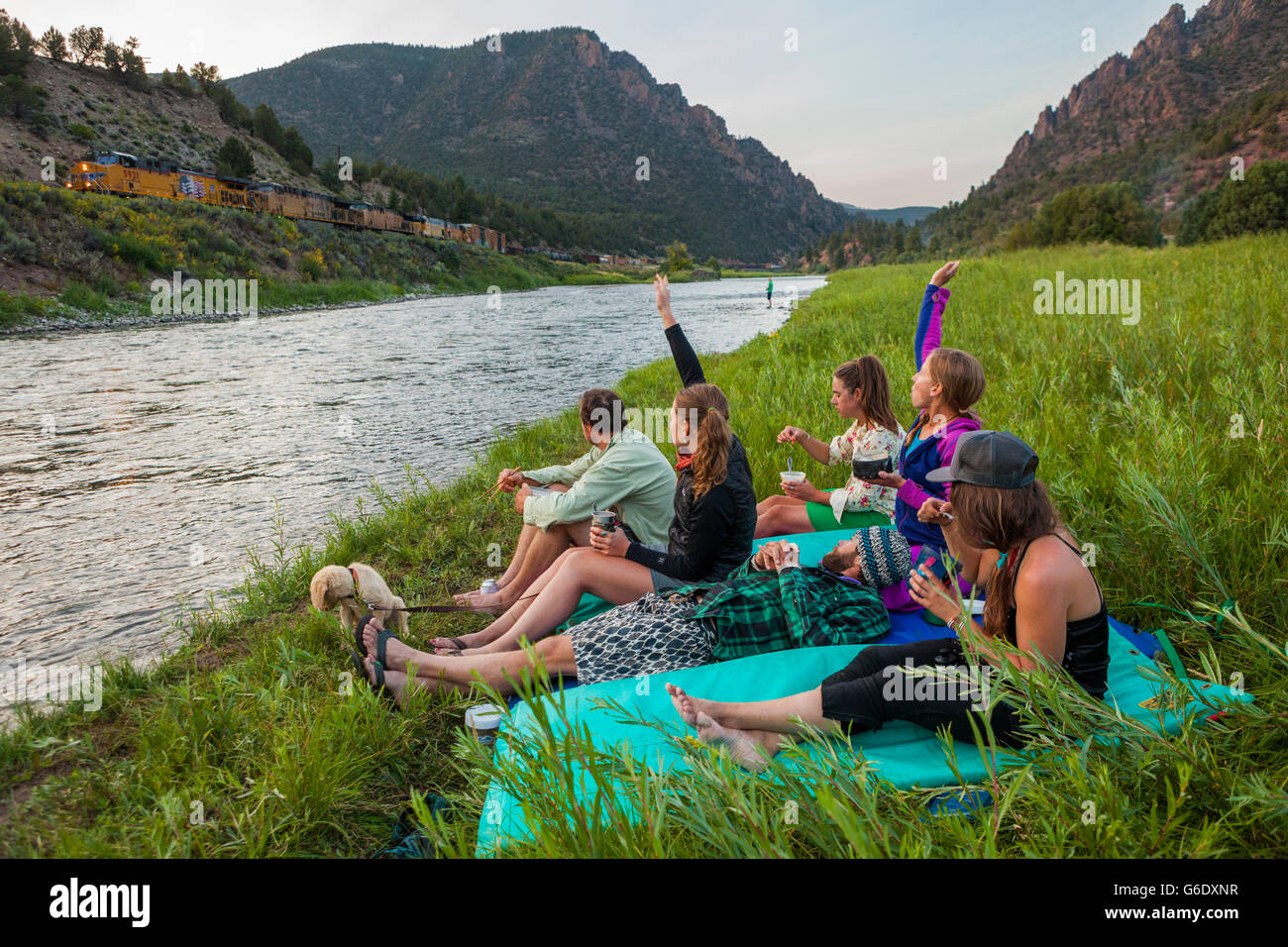Boaters wave at a passing freight train while eating dinner by the Upper Colorado River at the Benches Campground - Stock Image