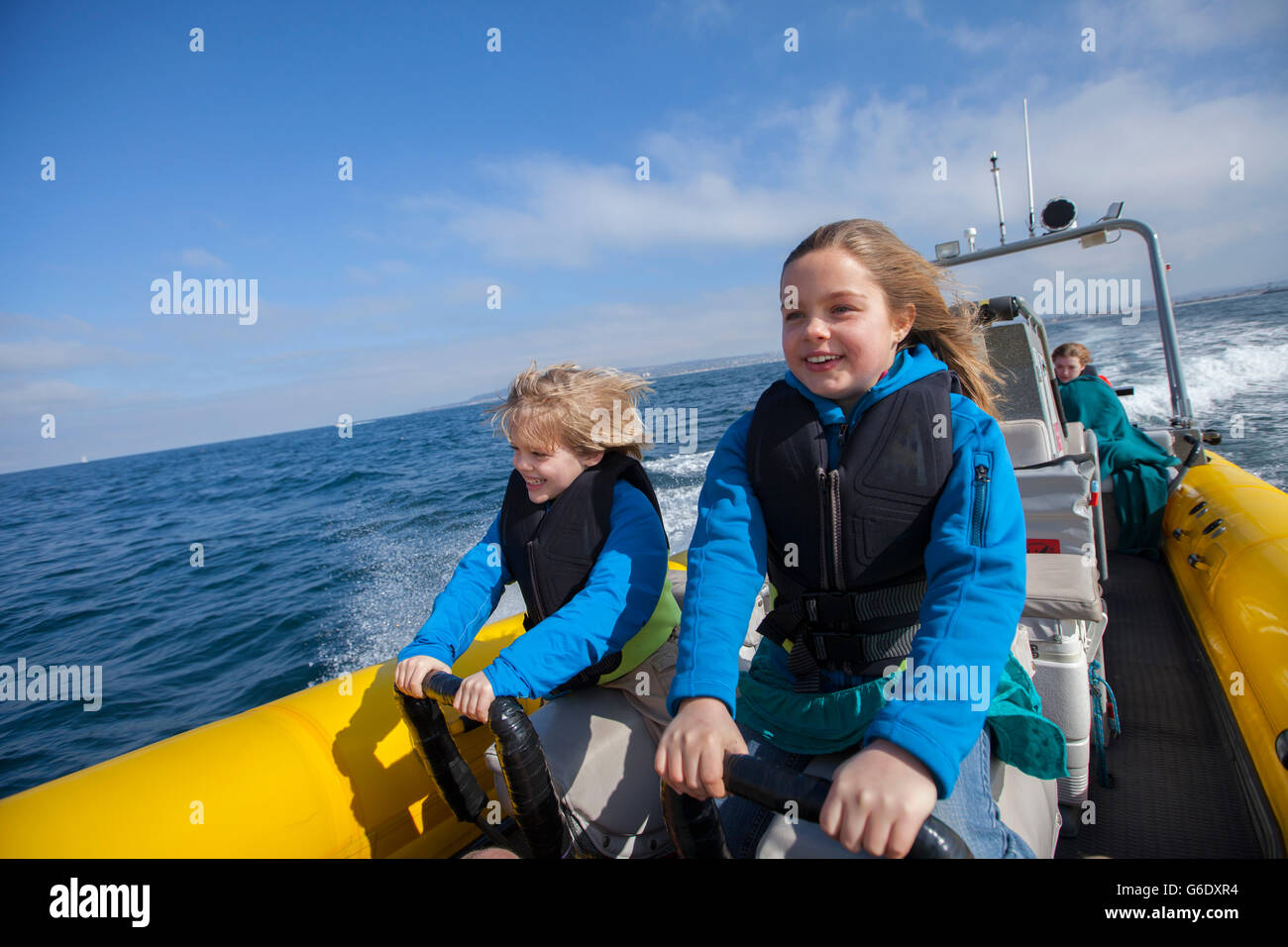 Two children loving the thrill of the ride with Captain Russell Moore of Xplore Offshore, San Diego's original - Stock Image