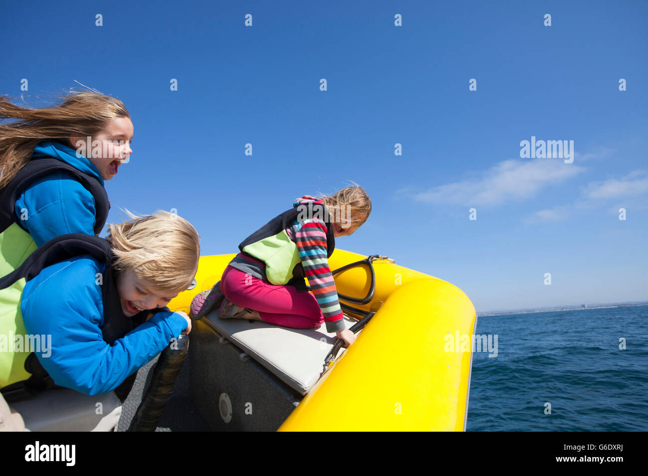 Three children ages 5, 8, and 9 loving the thrill of the ride with Xplore Offshore, San Diego's original ocean - Stock Image