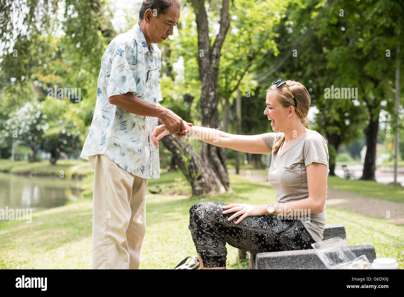 A man massages a woman's wrist while sitting in Lumphini Park on April 23, 2015. - Stock Image