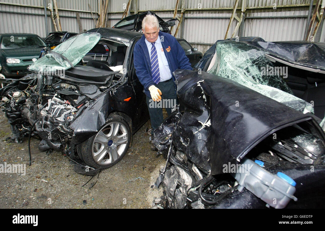 A member of staff looks at the remains of the Ford Mondeo and Audi cars, at a recovery yard in Newry, County Down, Stock Photo