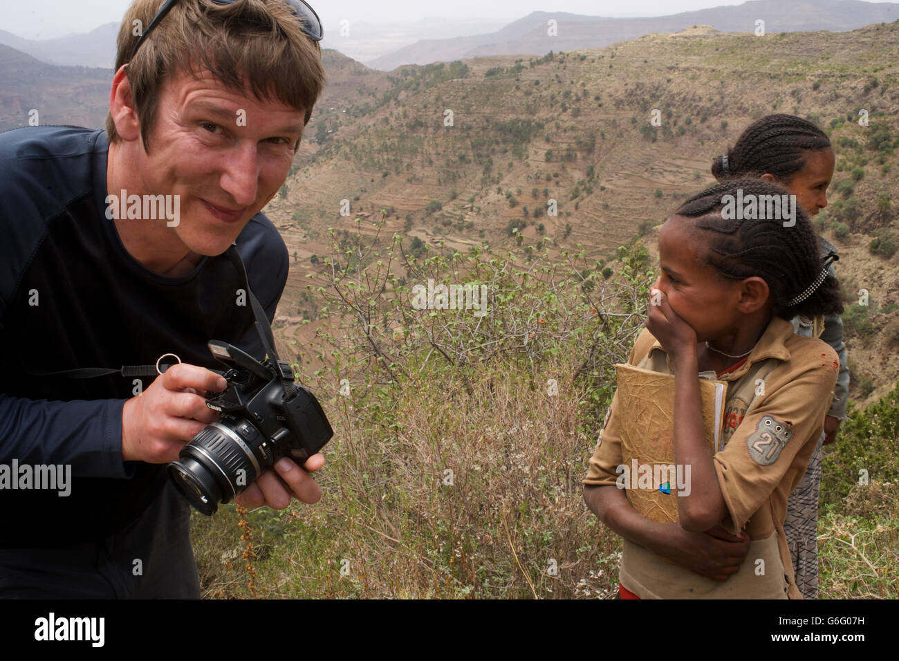 Western traveller sharing his digital photographs with Ethiopian kids. Tigray, Ethiopia. - Stock Image