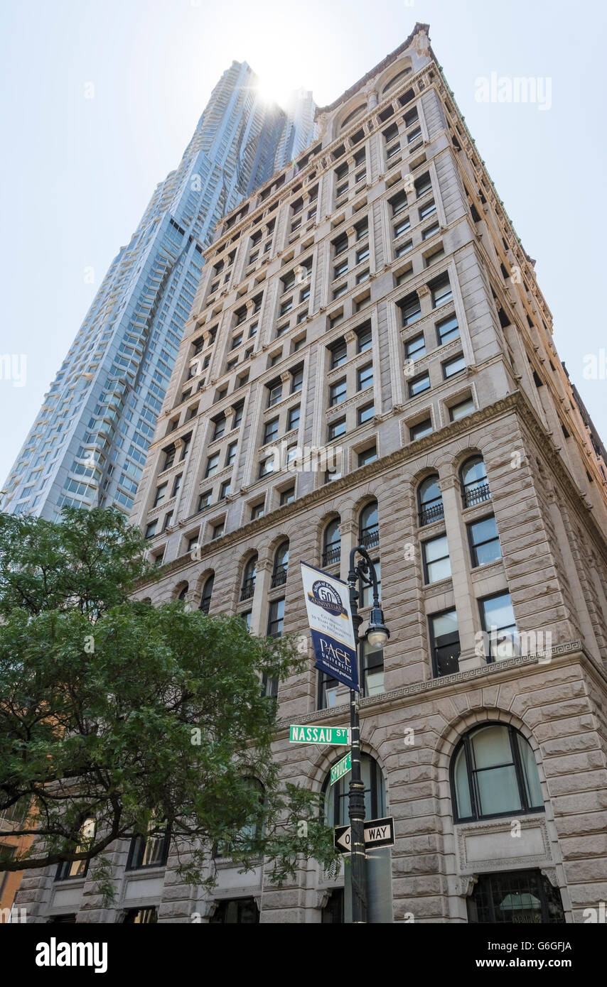 Low angle view of the landmarked American Tract Society Building with New York by Frank Gehry behind and sun flare. - Stock Image