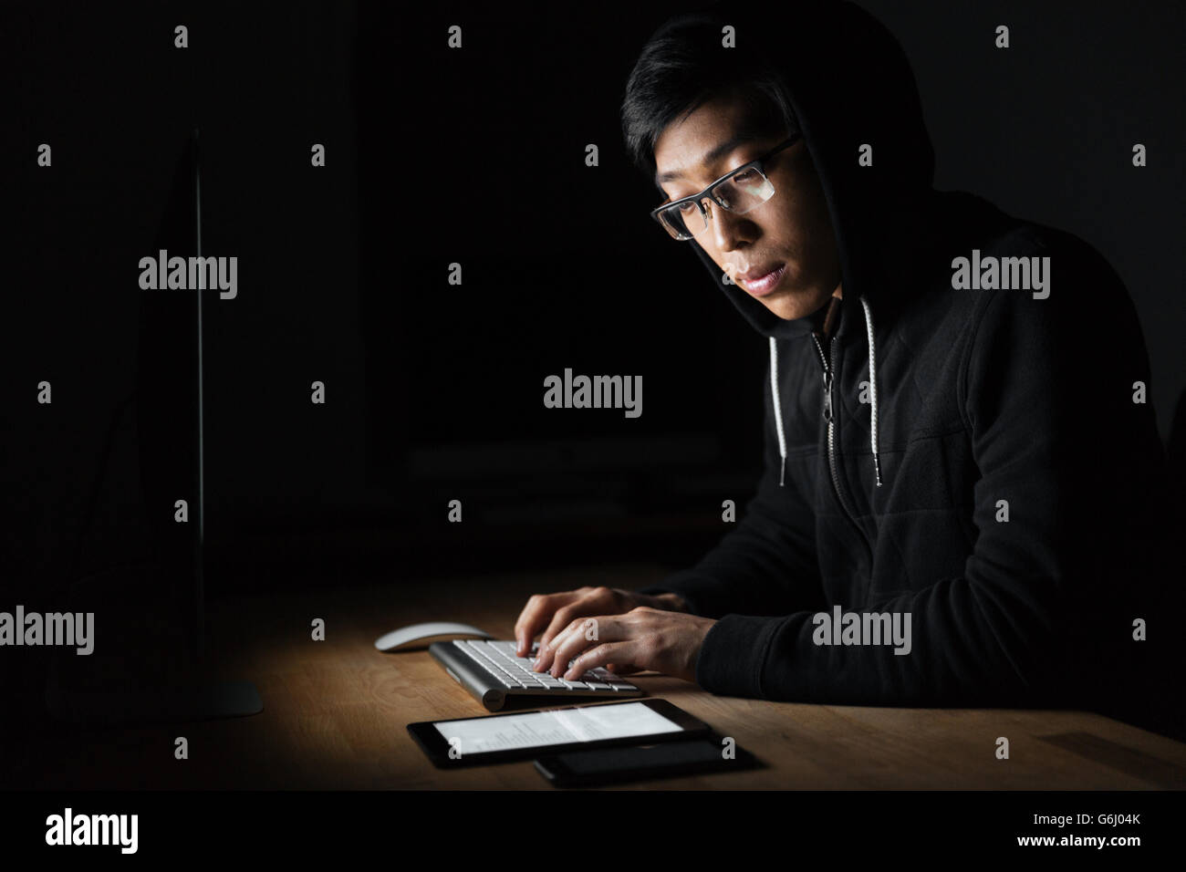 Hacker sitting and using laptop, tablet and smartphone in dark room - Stock Image