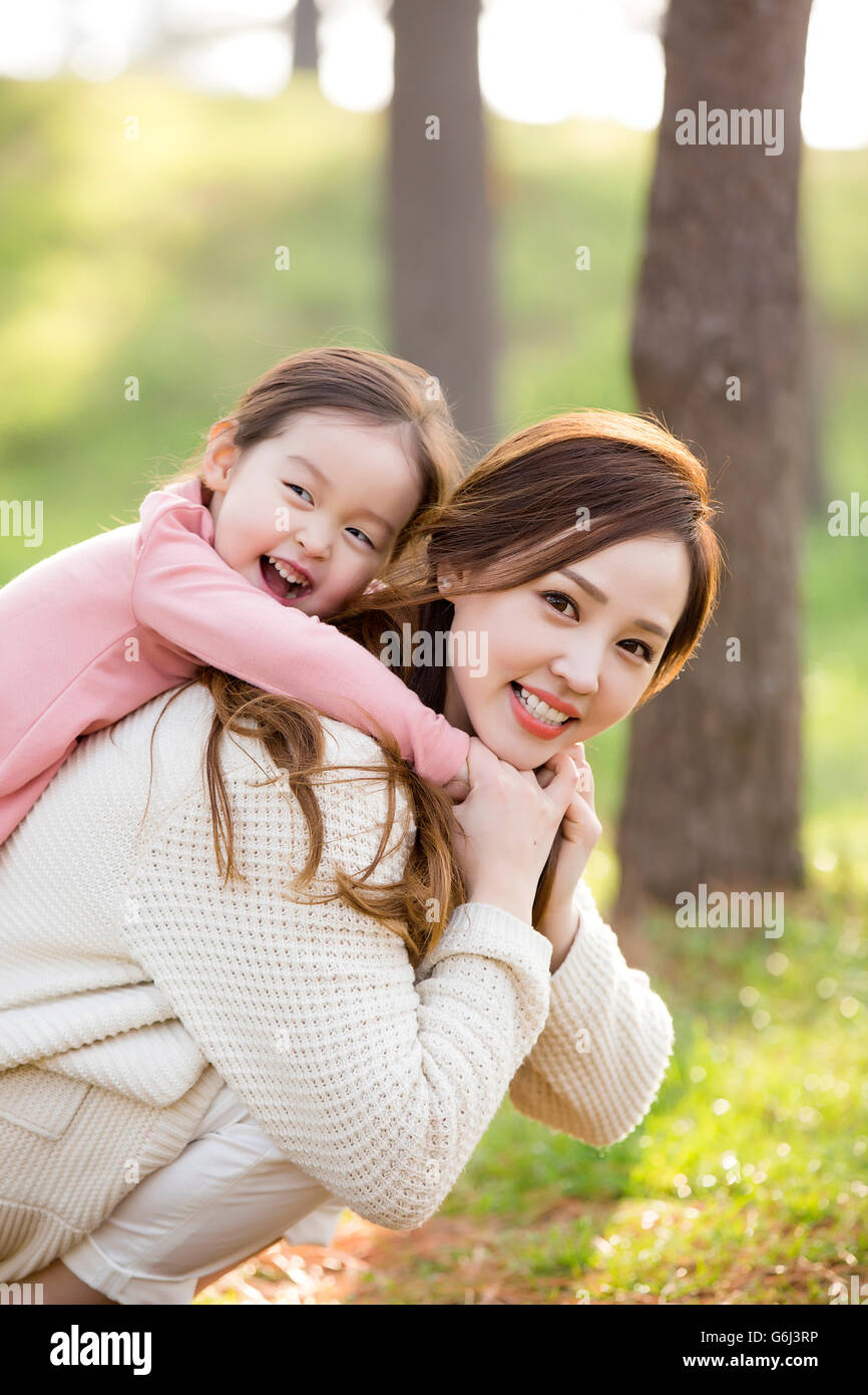 Happy Asian Mother and Daughter Smiling and Posing in Forest - Stock Image