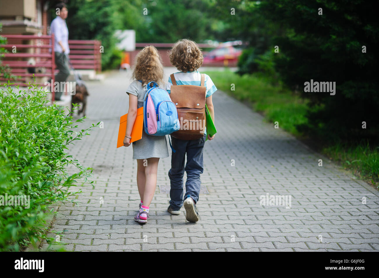 Two pupils of primary school go hand in hand. Boy and girl with school bags behind the back. Beginning of school - Stock Image