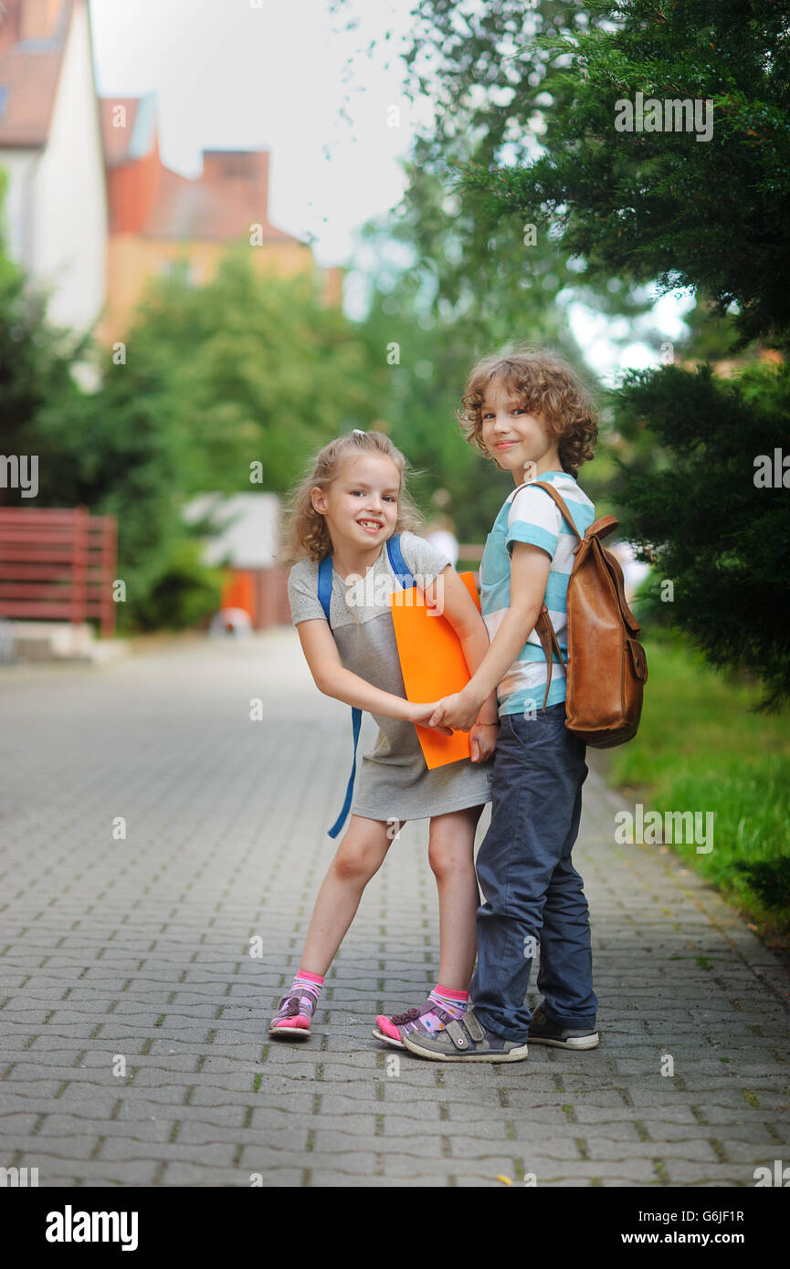Two pupils of elementary school, boy and girl, on the way to school. Children have a good mood. They hold hands - Stock Image