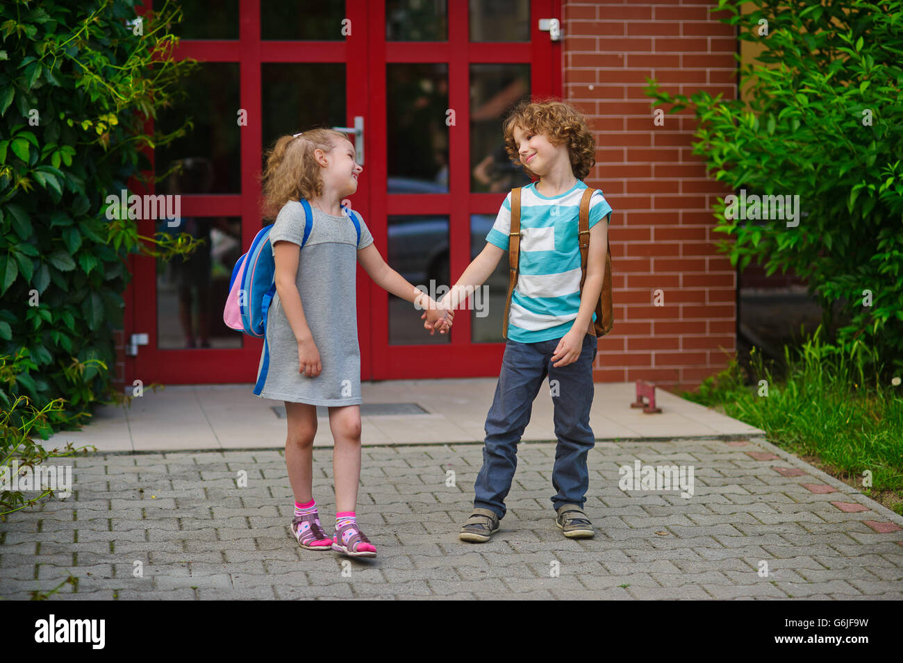 Little school students go on a schoolyard holding hands. Children with a smile look at each other. Boy and girl. - Stock Image