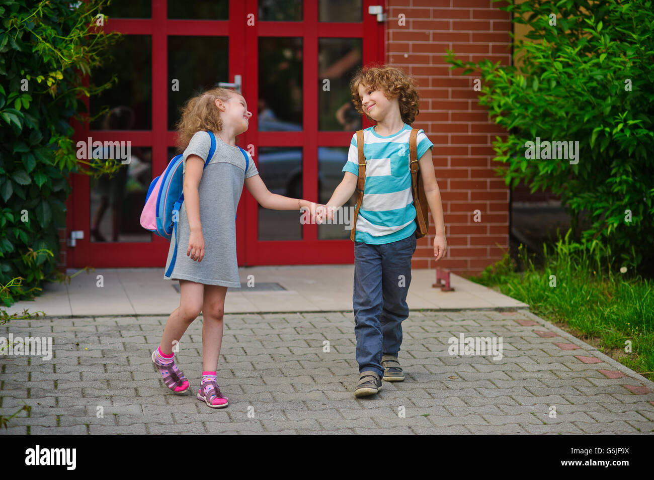 Little school students go on a schoolyard holding hands. Children with a smile look at each other. Boy and girl. Stock Photo