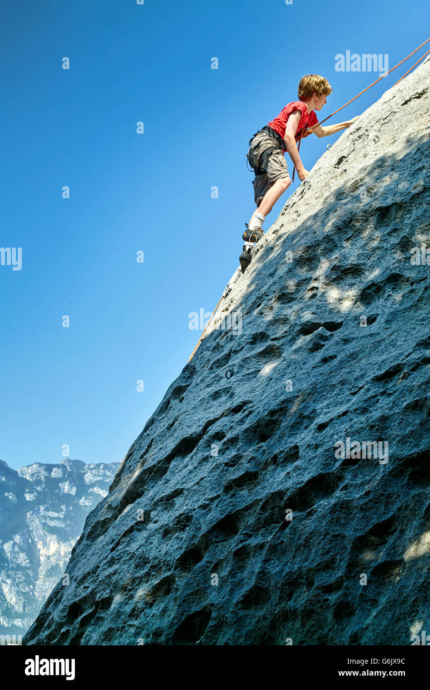 young boy is climbing to the top of a mountain. - Stock Image
