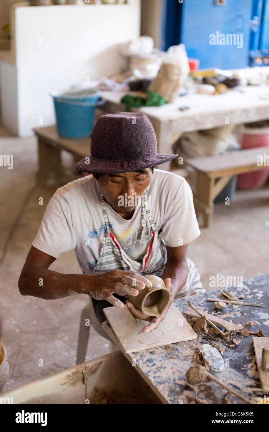 Potter in workshop working on earthenware jar - Stock Image