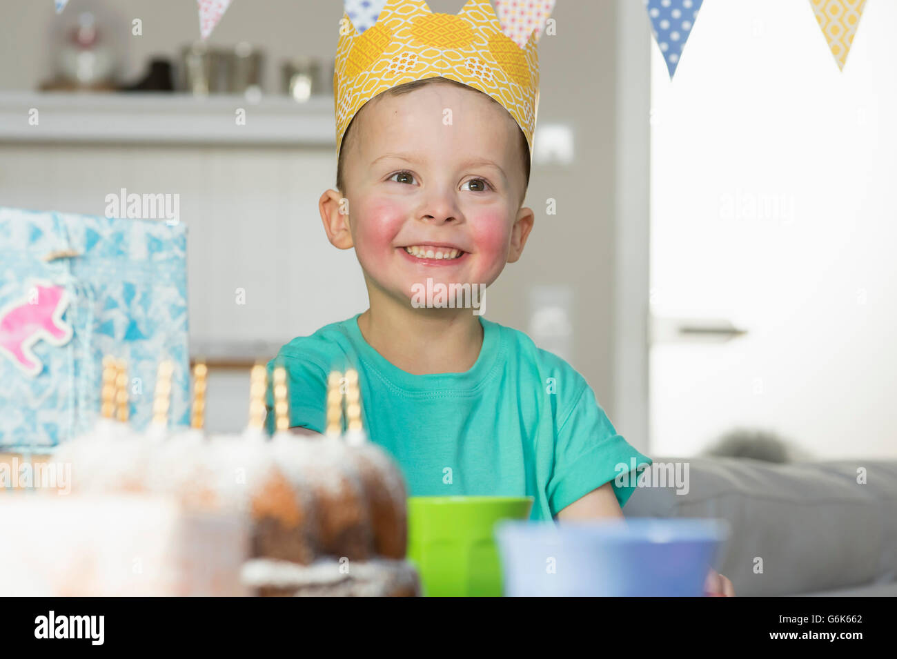0d54490725077 Happy boy wearing paper crown sitting at birthday table Stock Photo ...