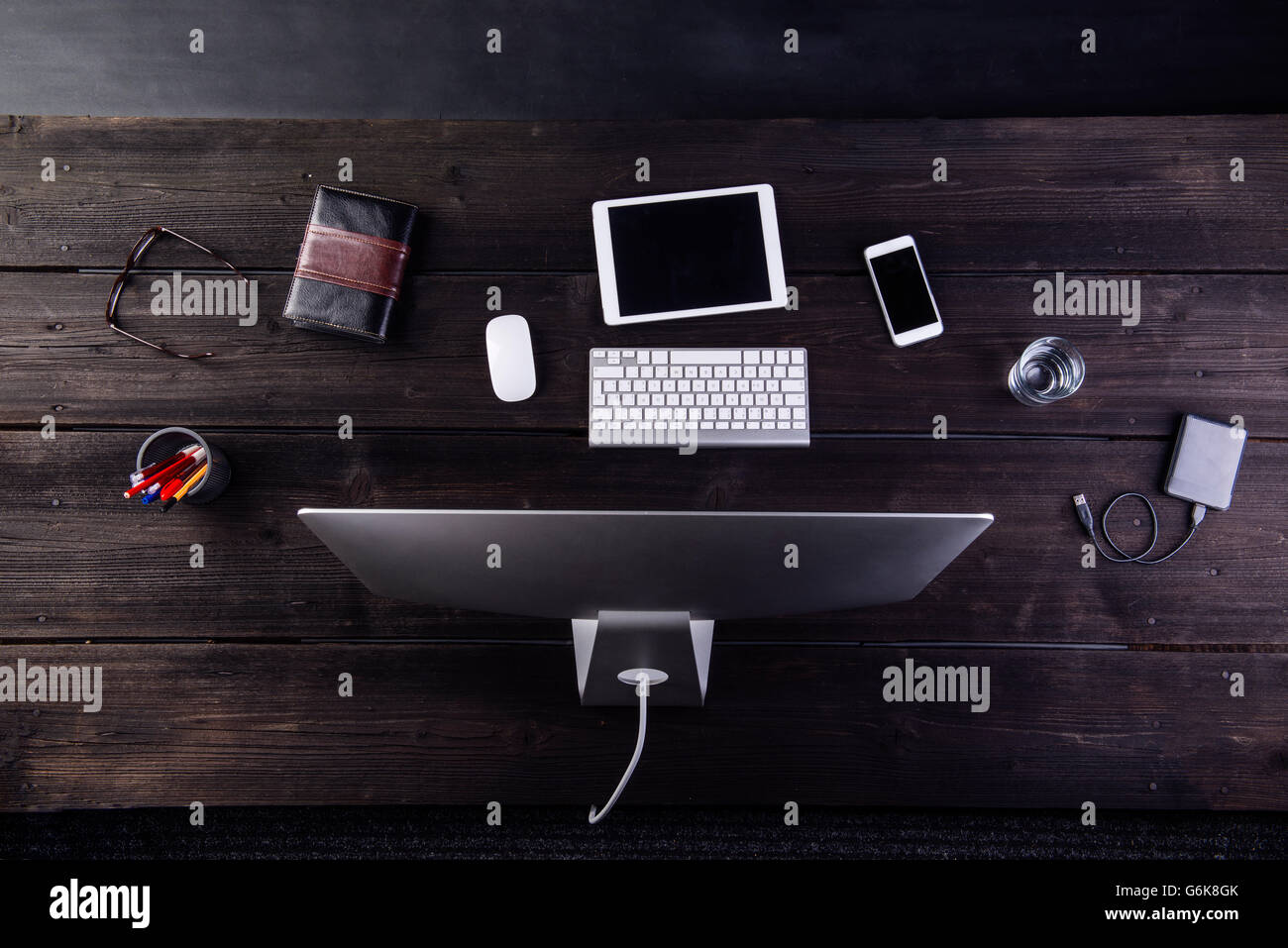 Desk with computer and various digital gadgets - Stock Image