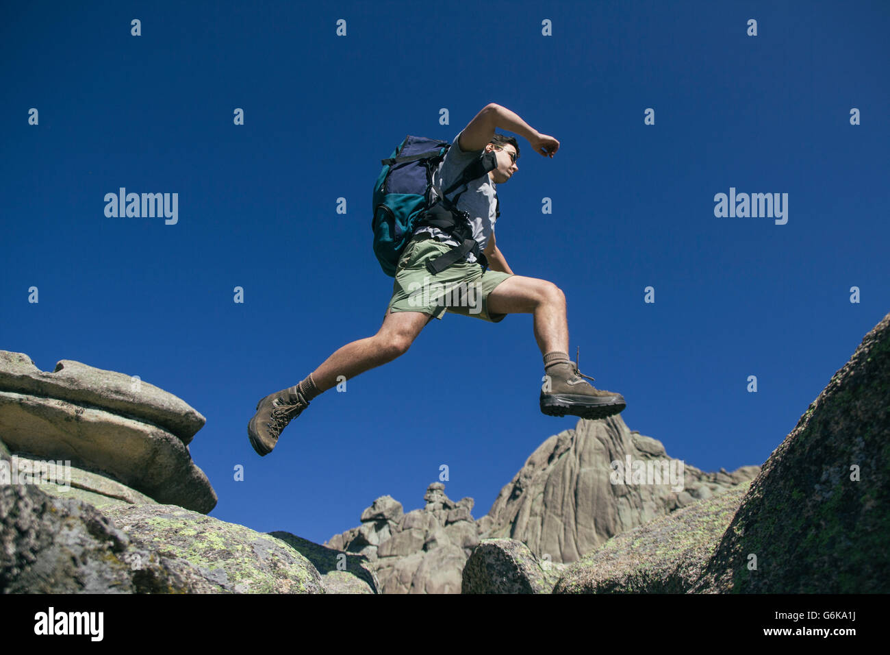 Spain, hiker with backpack jumping on the rocks in La Pedriza Stock Photo