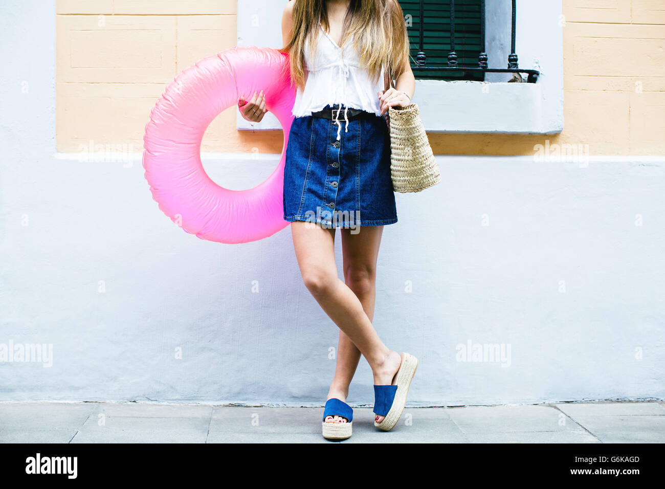 Young woman standing with bathing ring and beach bag Stock Photo ...