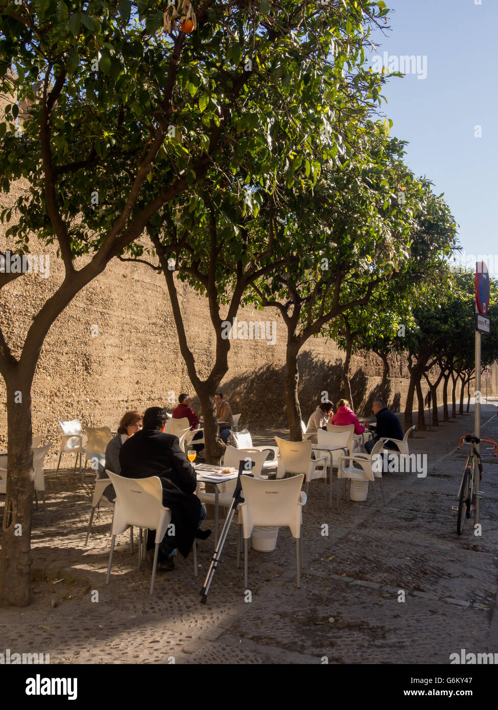 SEVILLE, SPAIN:  Cafe tables in the shadow of the city walls of Seville at Puerta de la Macarena - Stock Image