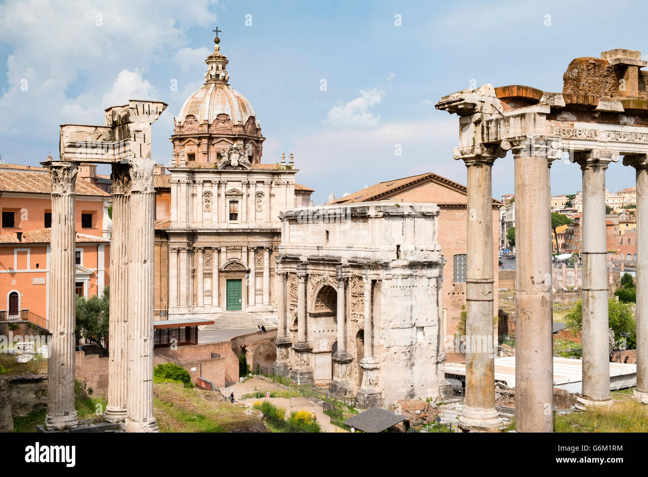 View of the Roman Forum with ruined columns of The Temple of Saturn on the right  in Rome, Italy - Stock Image