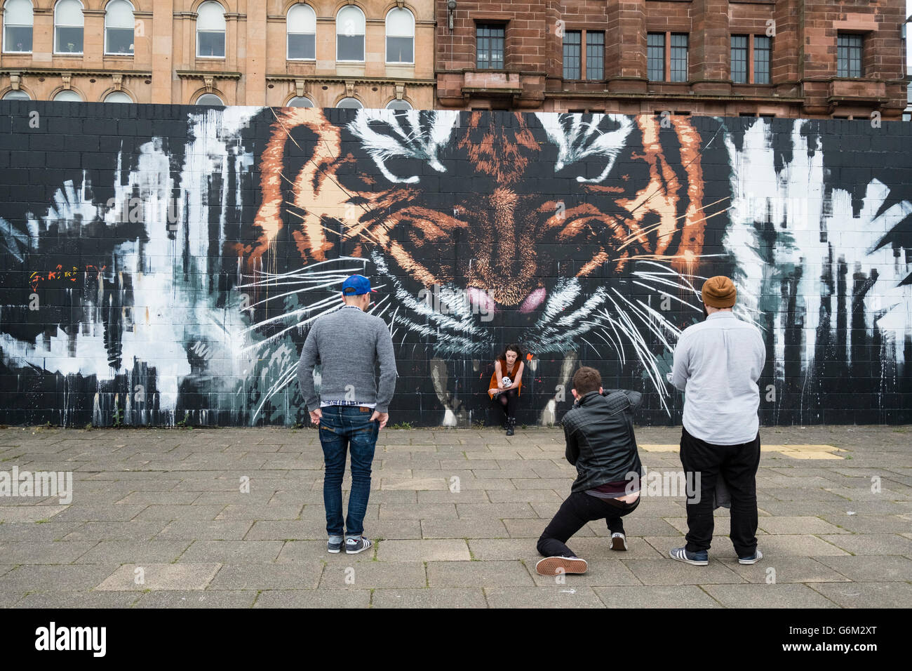 Street scene with tiger mural , street art on walkway beside River Clyde in central Glasgow , Scotland, United Kingdom - Stock Image