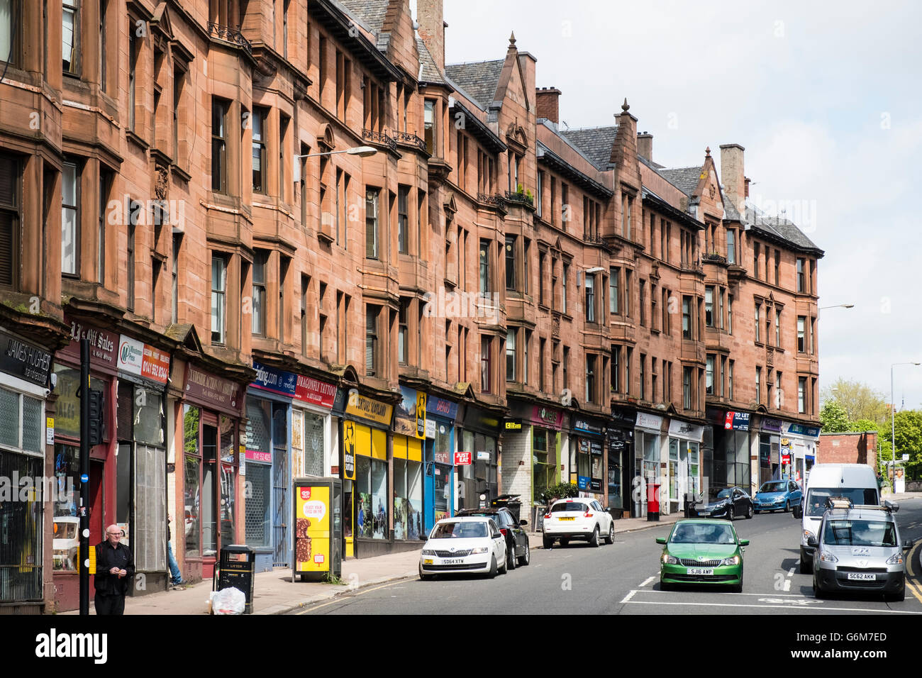 View along High Street with traditional sandstone tenement apartment buildings  in East End of Glasgow, Scotland, - Stock Image