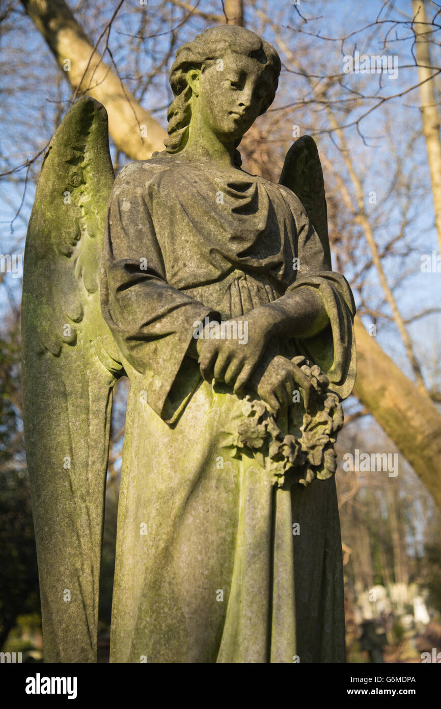close-up of stone sculpture of angel on sunny winter's day in Highgate cemetery, north London Stock Photo