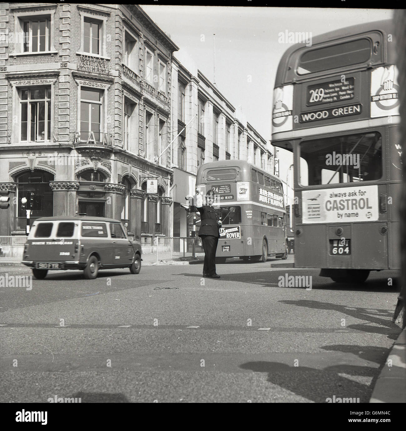 1950s, historical, policeman in the middle of the road directing traffic, London. - Stock Image