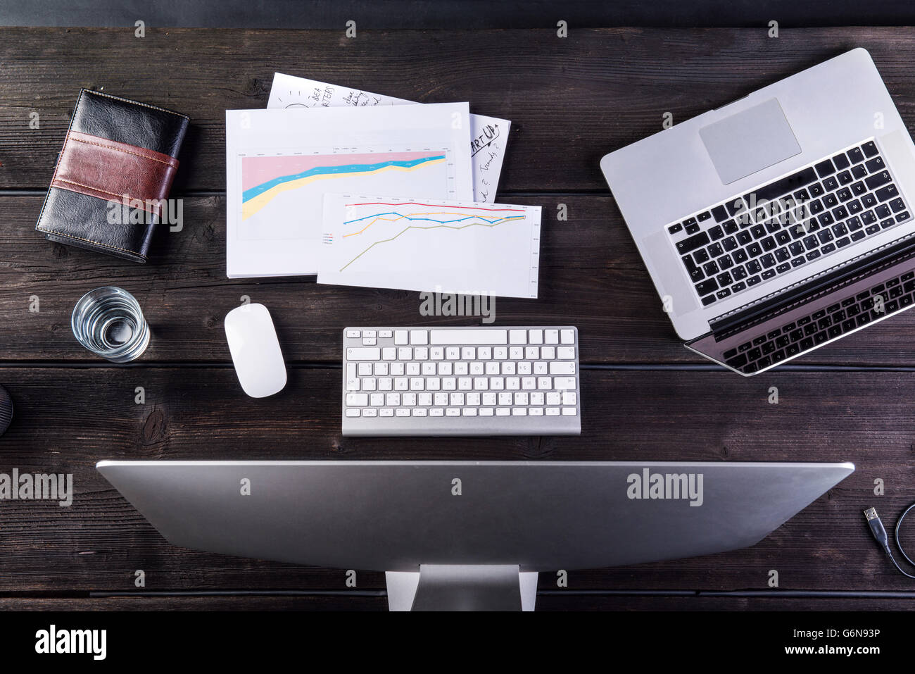 Desk with computers and charts, overhead view - Stock Image