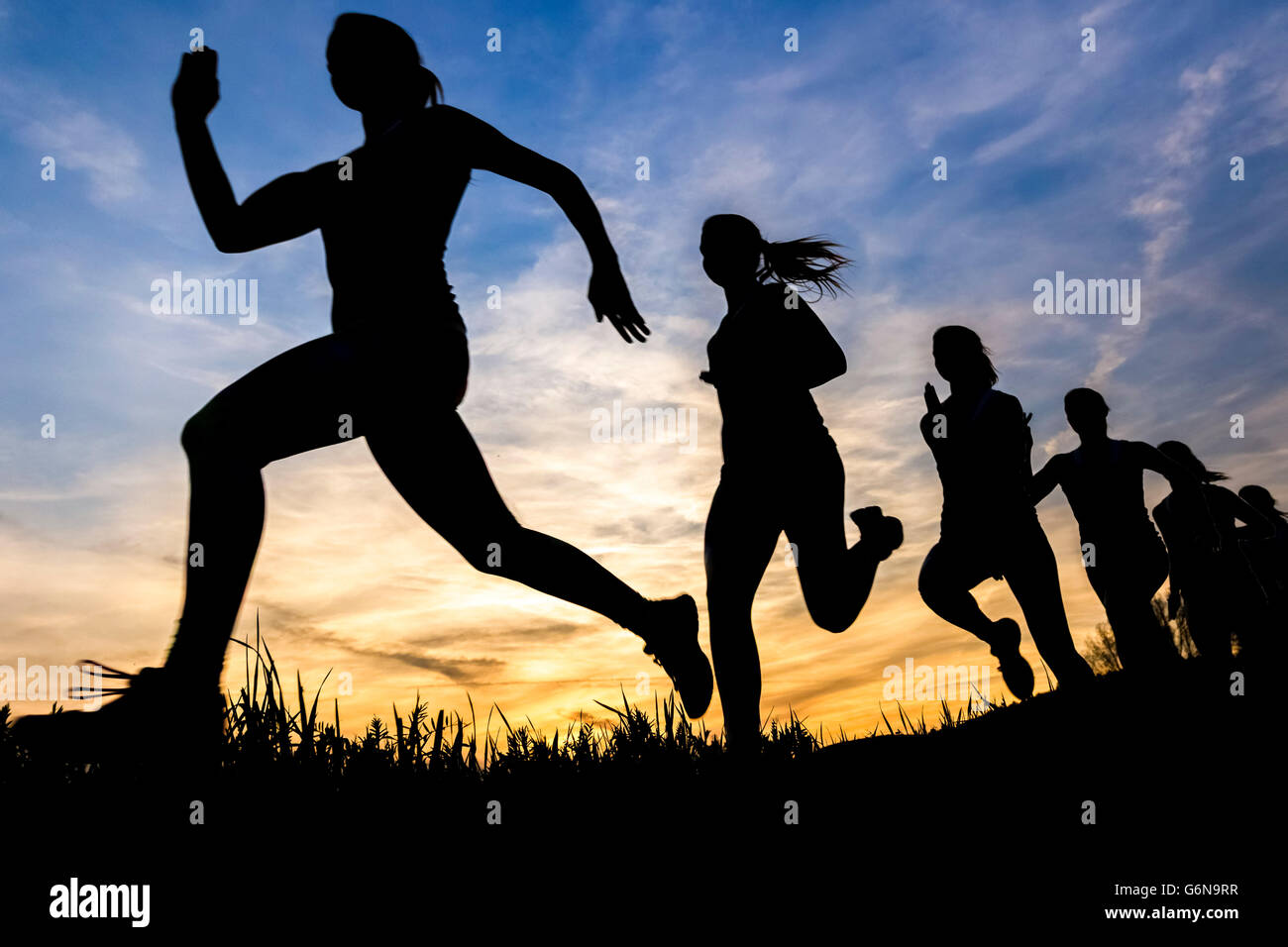 Silhouette of female jogger at sunset, sequence, phases - Stock Image