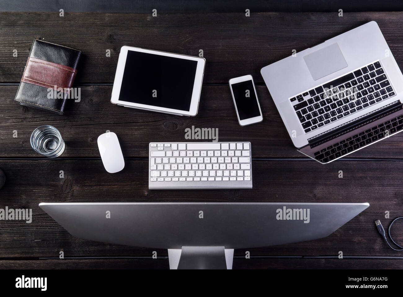 Desk with computer and various digital gadgets, overhead view - Stock Image