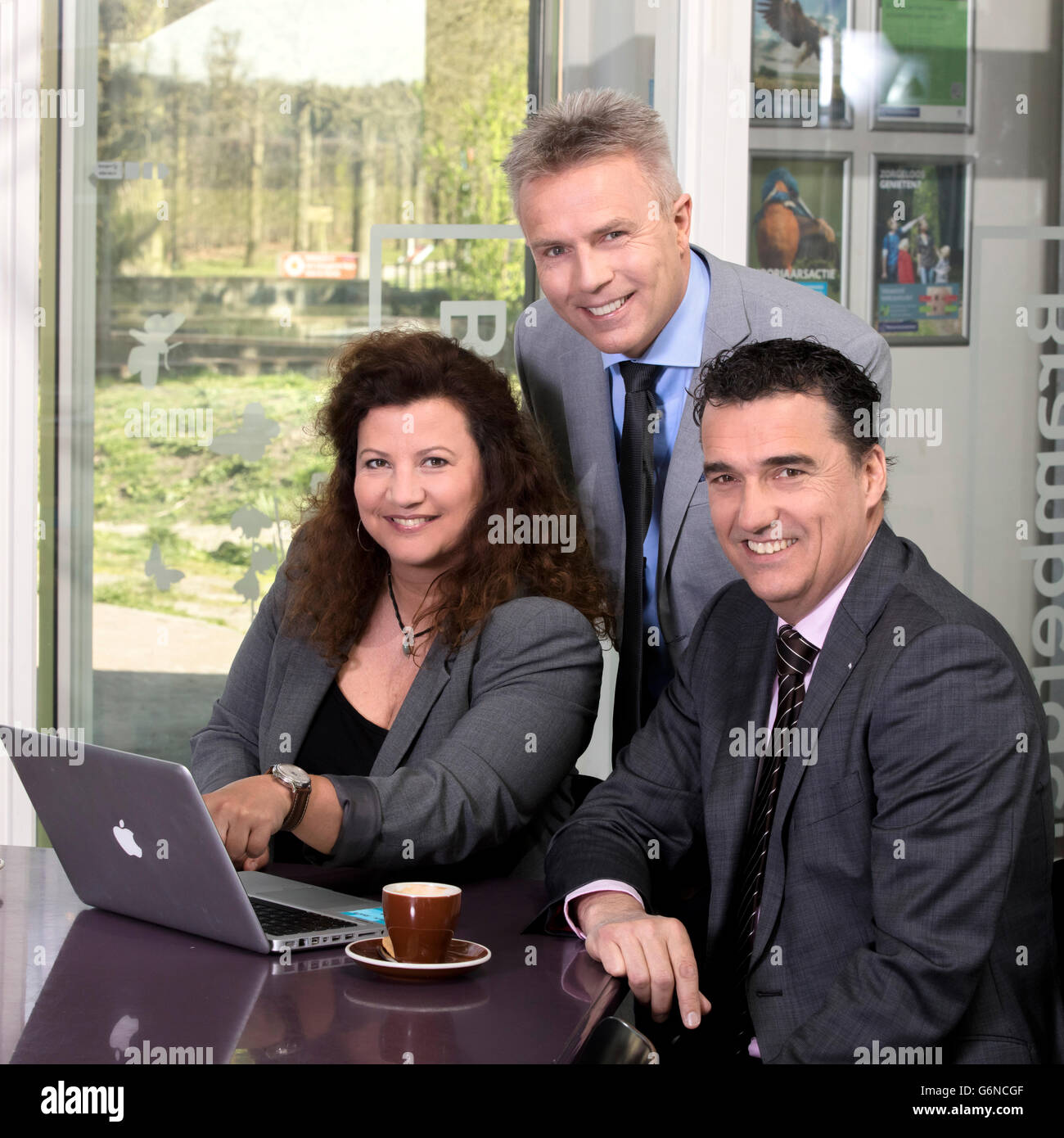 Portrait happy business people behind laptop look at camera in a large cooperate modern office, coffee and strategy - Stock Image