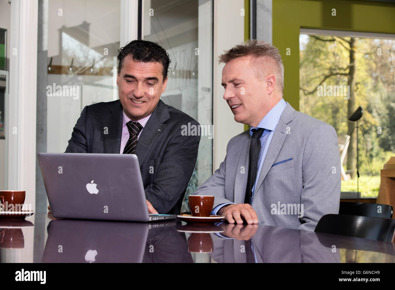 Confident and successful business partners brainstorming ideas in a large cooperate modern office, could also be - Stock Image