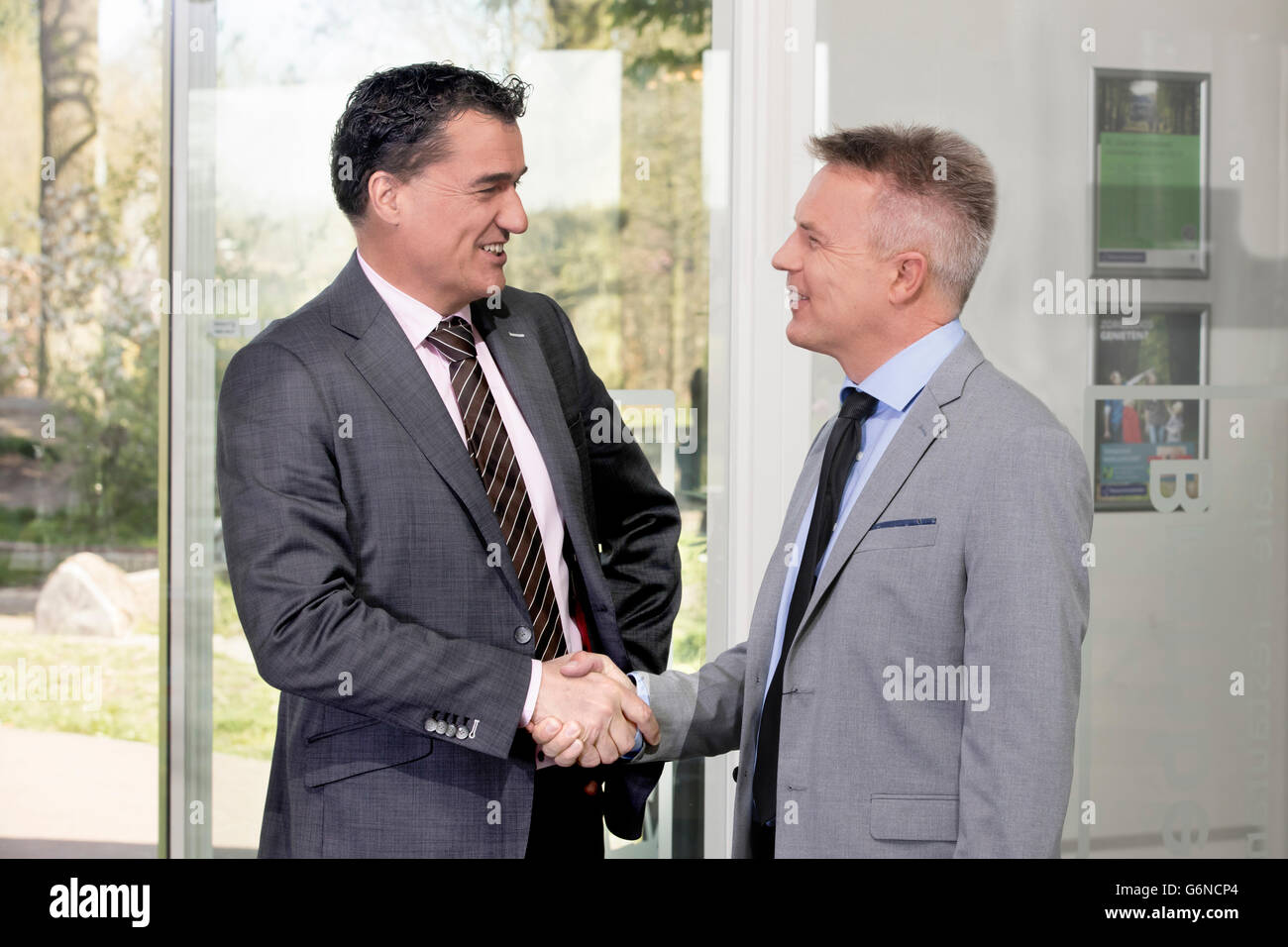 Confident and successful business men shaking hands in a large cooperate modern office - Stock Image