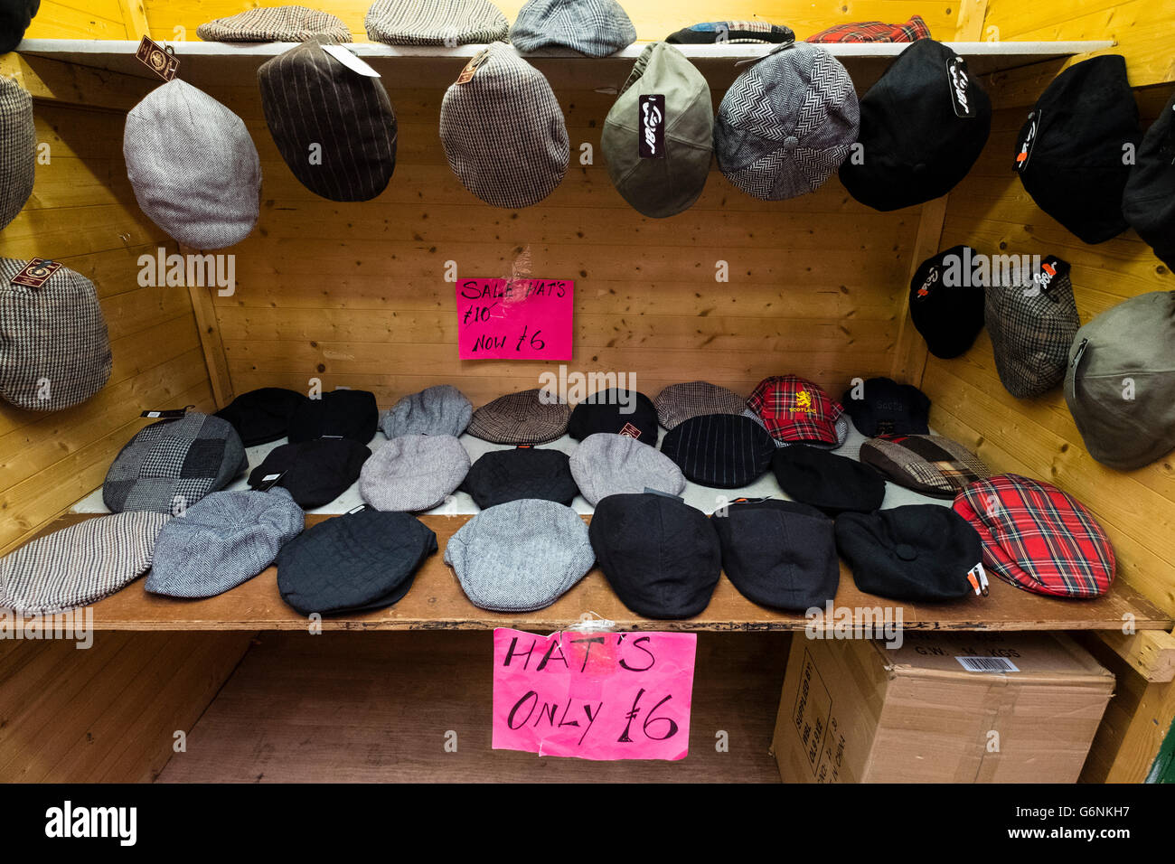 Traditional cloth caps for sale on stall at Barras Market in Gallowgate Glasgow, United Kingdom - Stock Image
