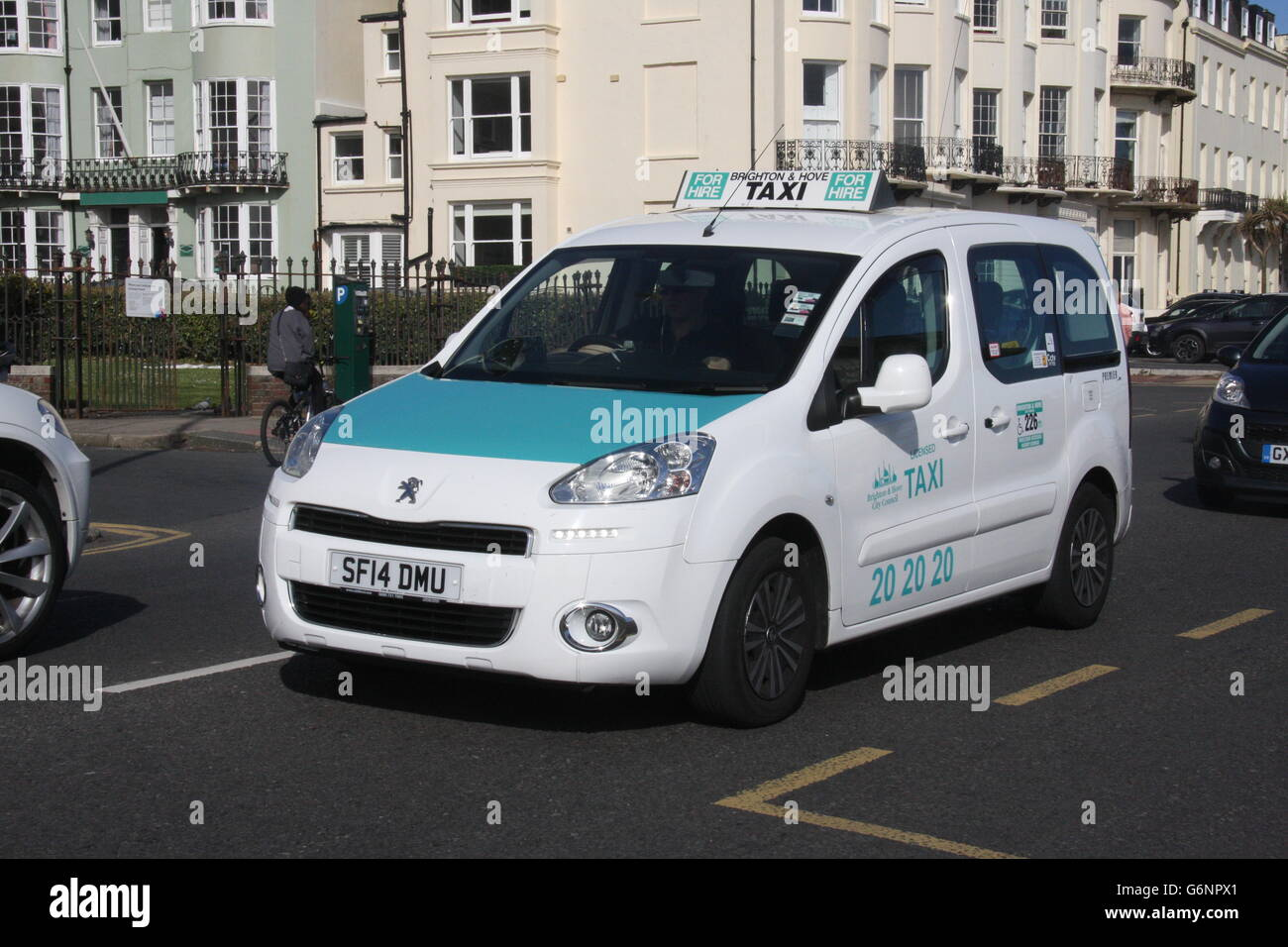 A SUNNY NEARSIDE VIEW OF A PEUGEOT TAXI CAB IN BRIGHTON - Stock Image