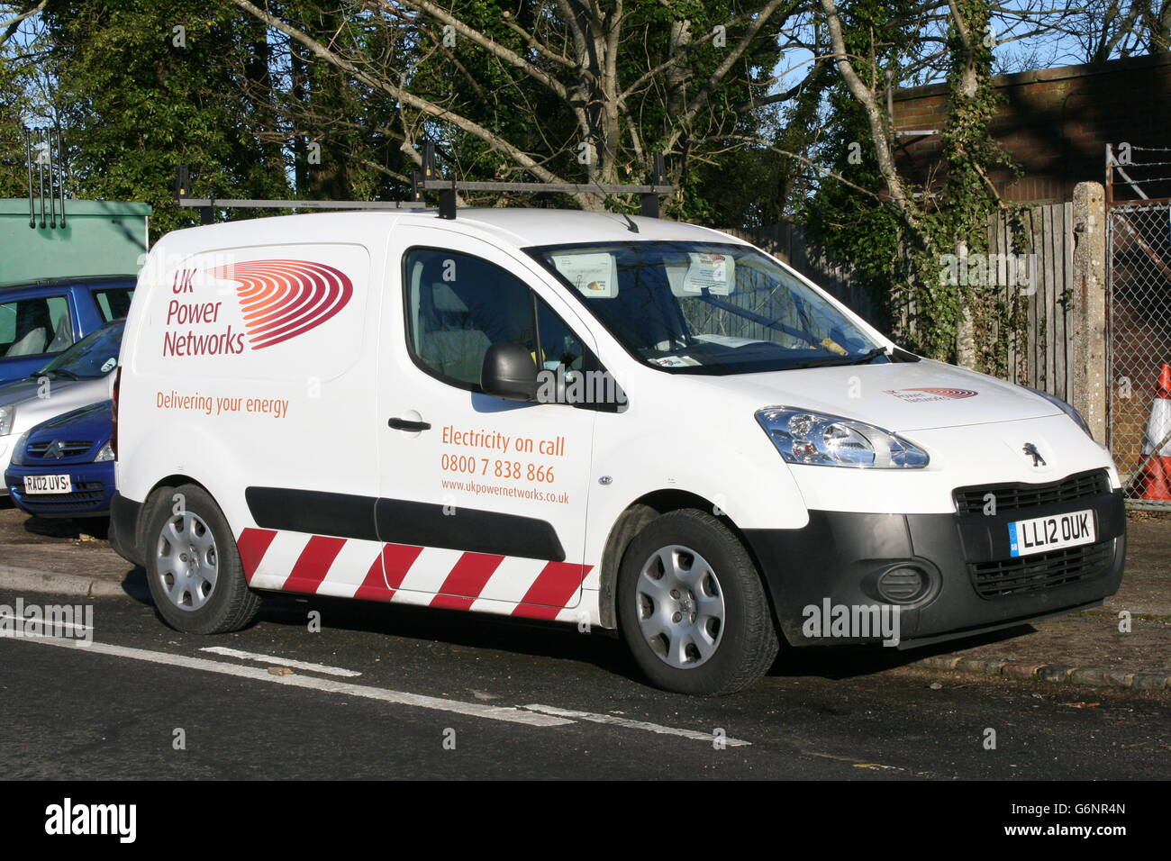 A SUNNY OFFSIDE VIEW OF A UK POWER NETWORKS SMALL PEUGEOT VAN - Stock Image