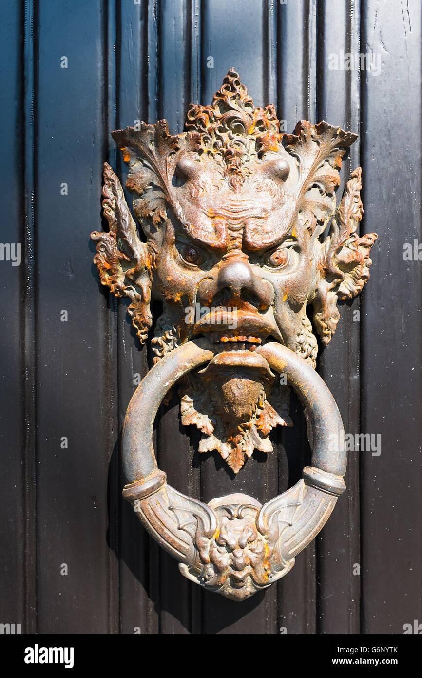 A rusty door knocker depicting the horned head of a devil or demon on the door of a building in the Villa Monastero Lake Como & A rusty door knocker depicting the horned head of a devil or demon ...
