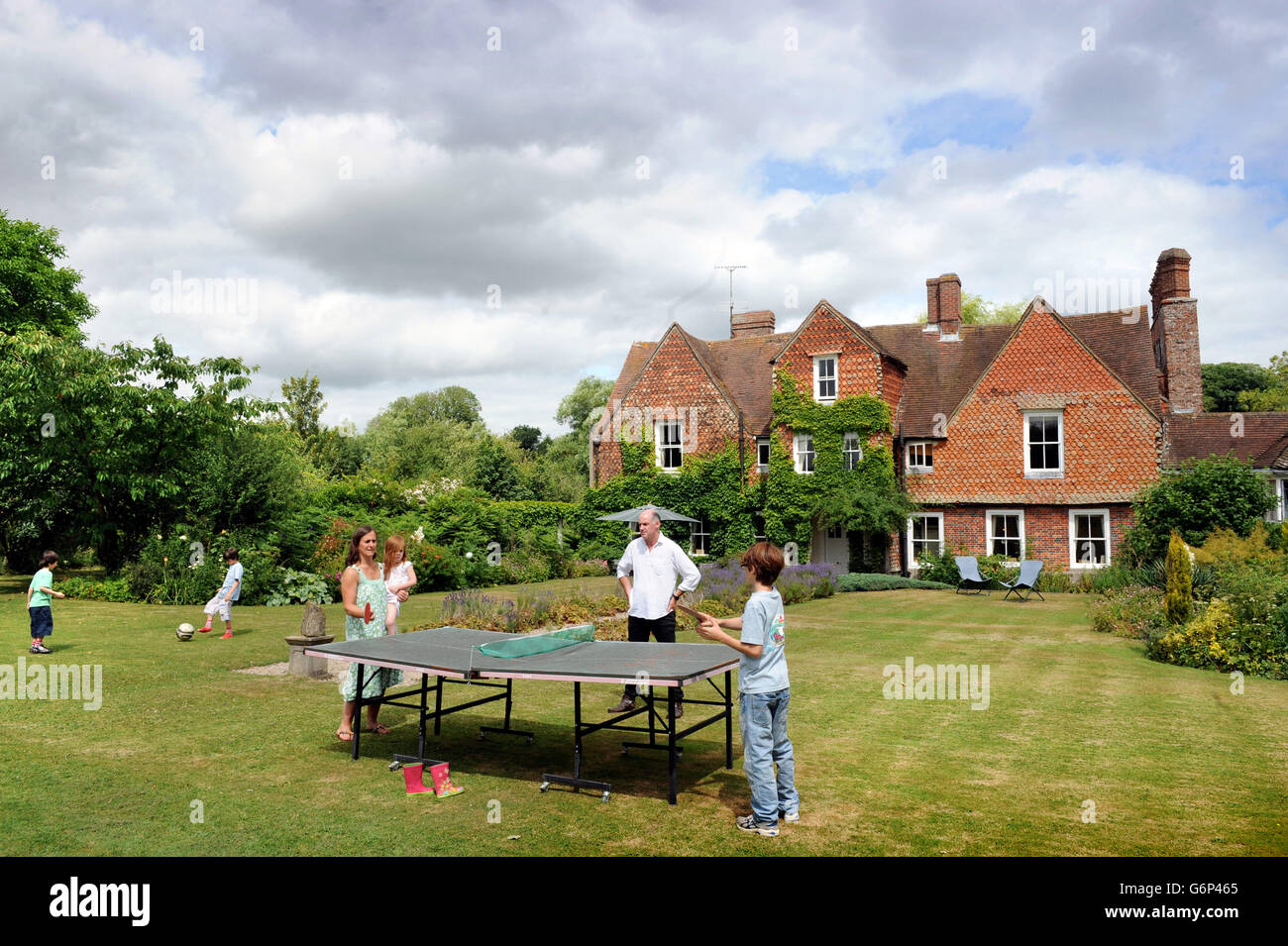 A family playing table tennis in the garden UK - Stock Image