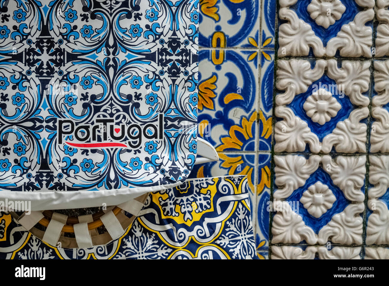 Portugal souvenir shop items displayed on a wall, with Portuguese azulejo tiles in the background. - Stock Image