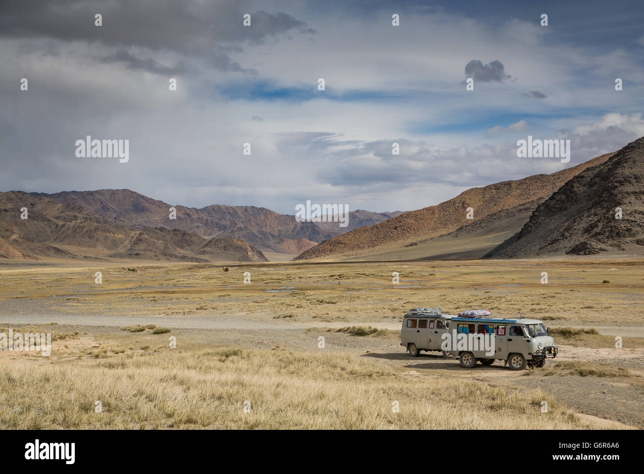 two cars next to the highway to west in western mongoliea - Stock Image
