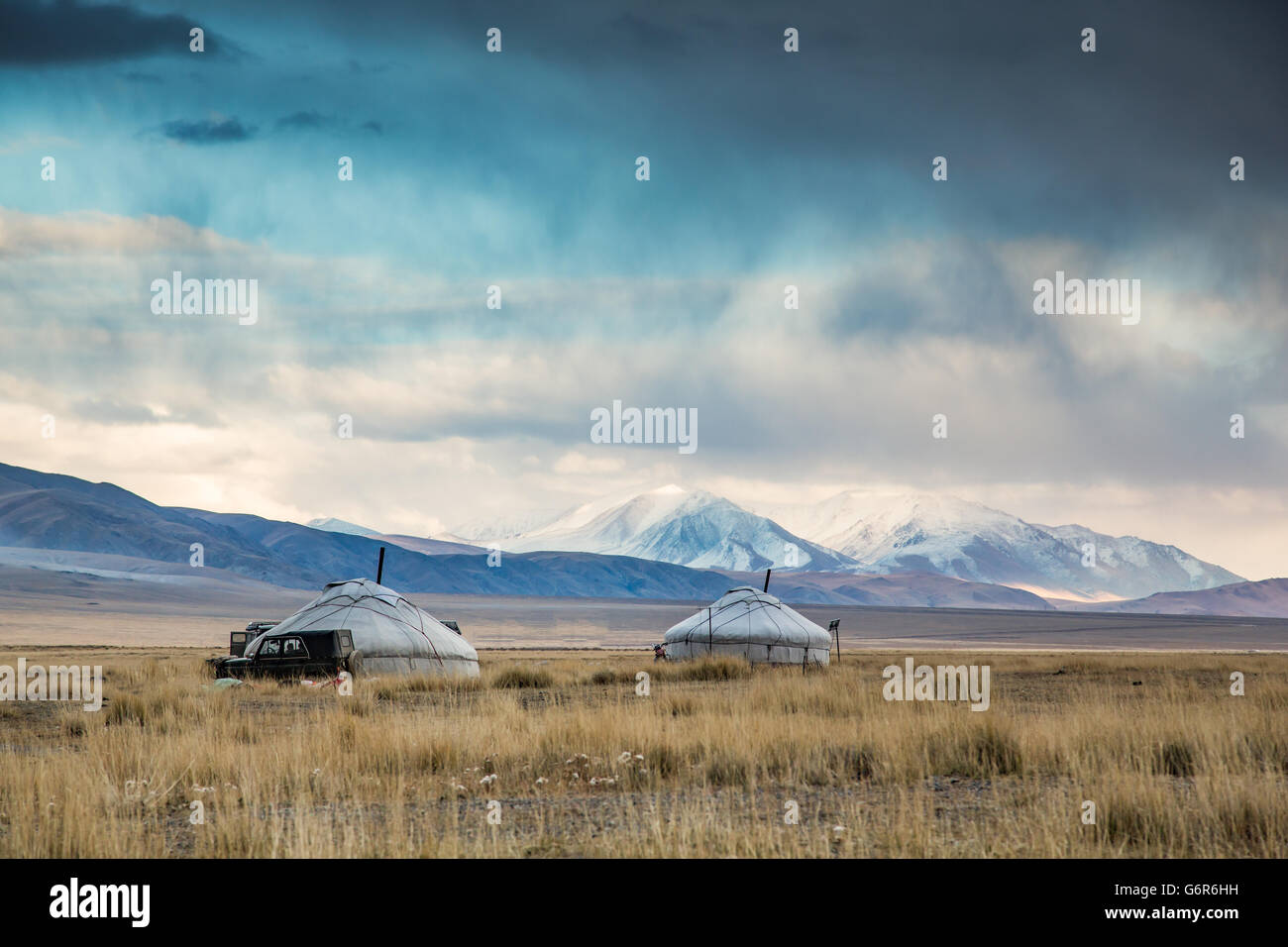 two yurts in a landscape of western Mongolia with snowy mountains at the backgrounds - Stock Image