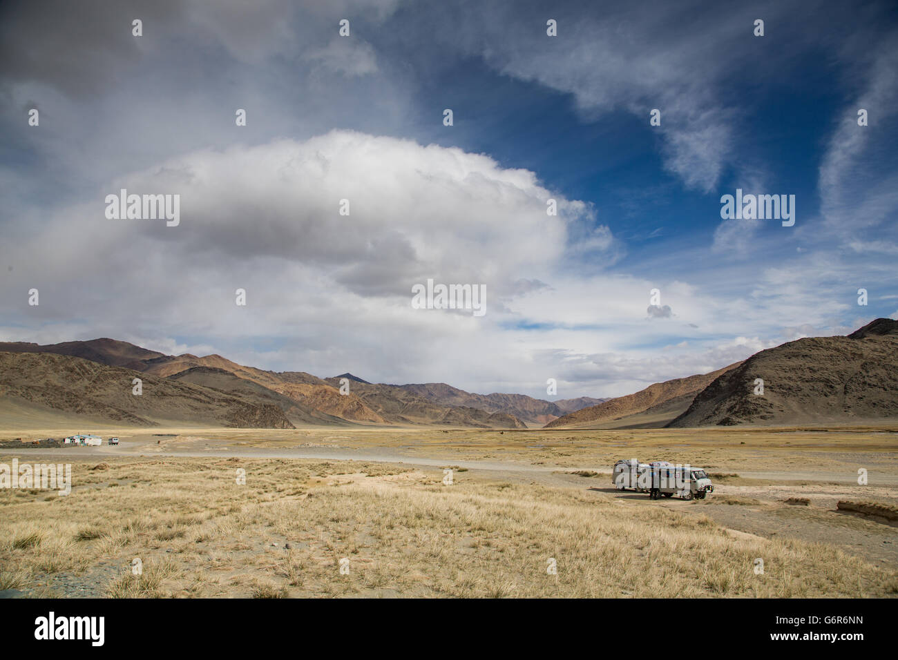 two cars on the side of a highway to west in the landscape of western Mongolia - Stock Image