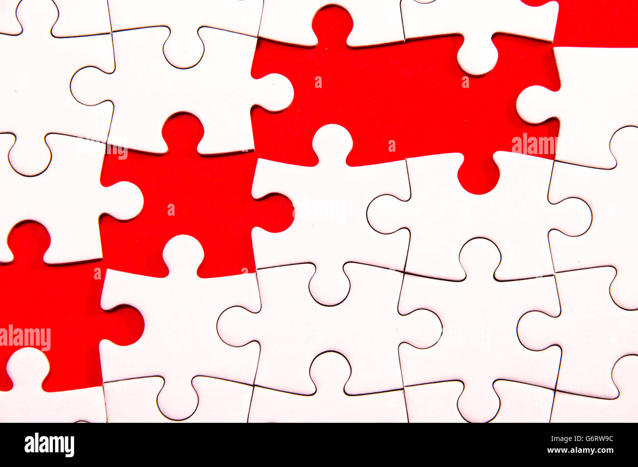 white jigsaw/puzzle wite some gaps over red background, symbol of problem solving - Stock Image