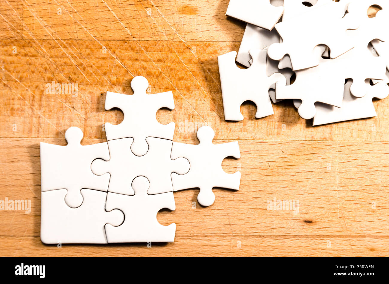 white jigsaw/puzzle unfinished over a wooden table background, symbol of problem solving - Stock Image
