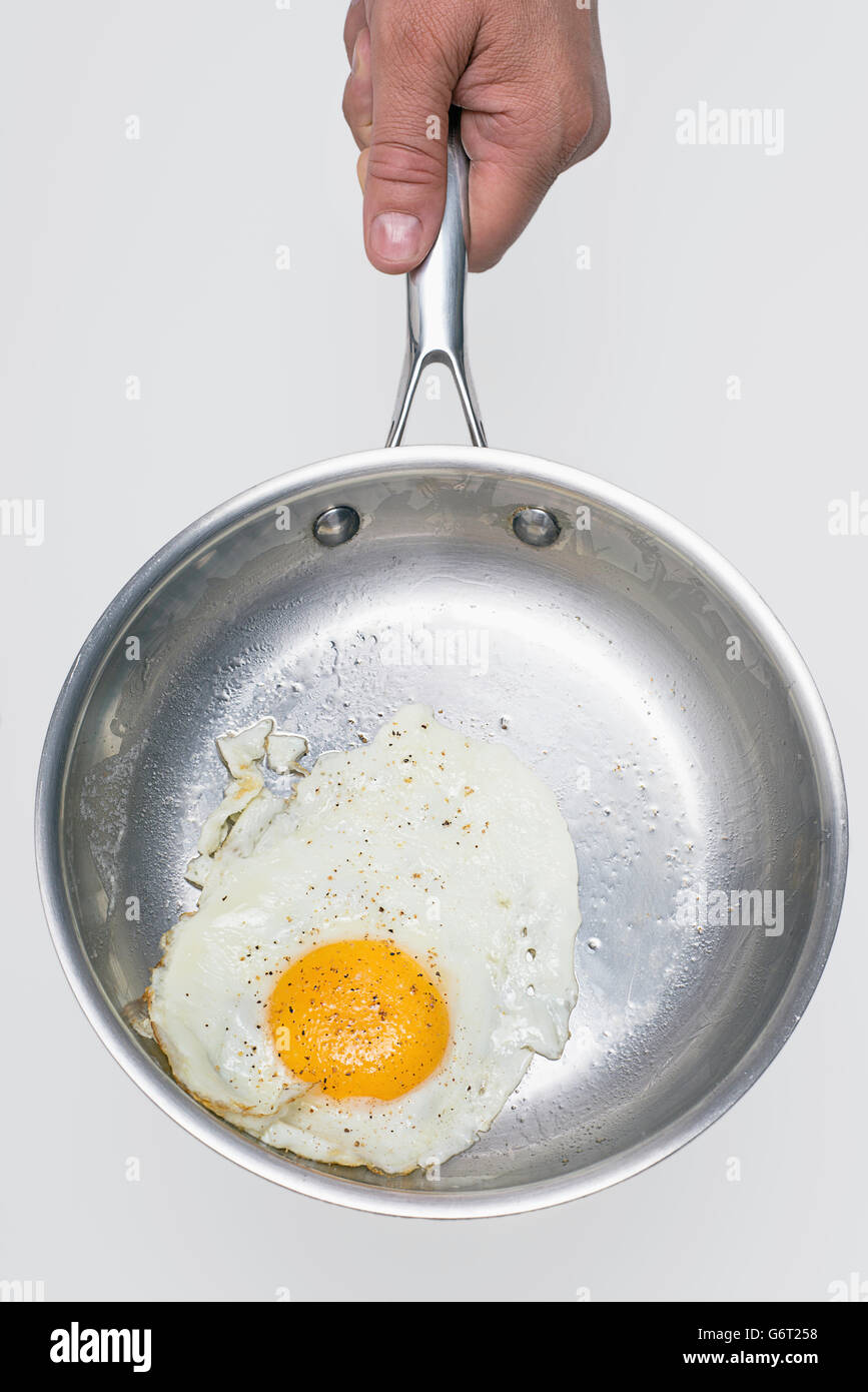 A fried egg in a pan. - Stock Image