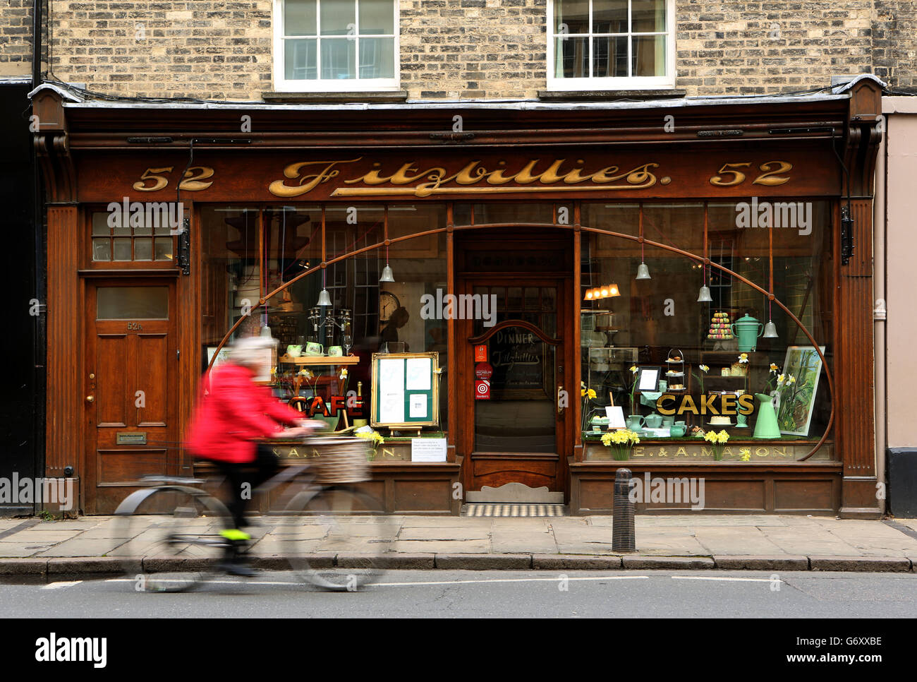A cyclist rides past Fitzbillies cake shop in Cambridge. Stock Photo