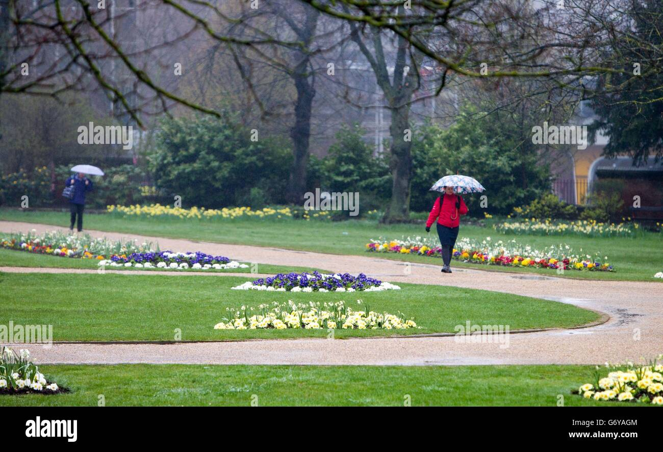 People walk in the rain at the Forbury Gardens in Reading, Berkshire. Stock Photo