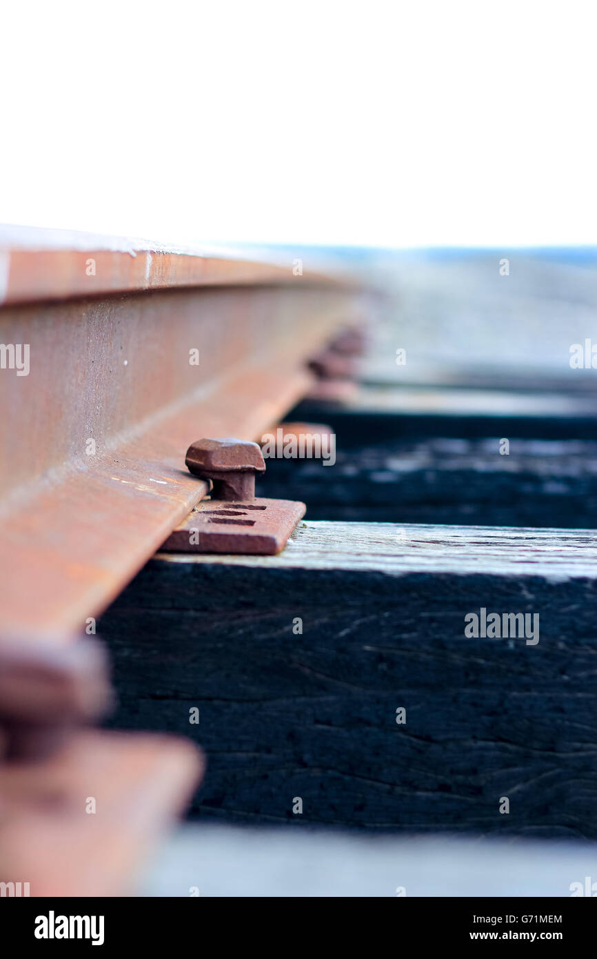 Close up of rusty railway lines crossing an old wooden bridge - Stock Image