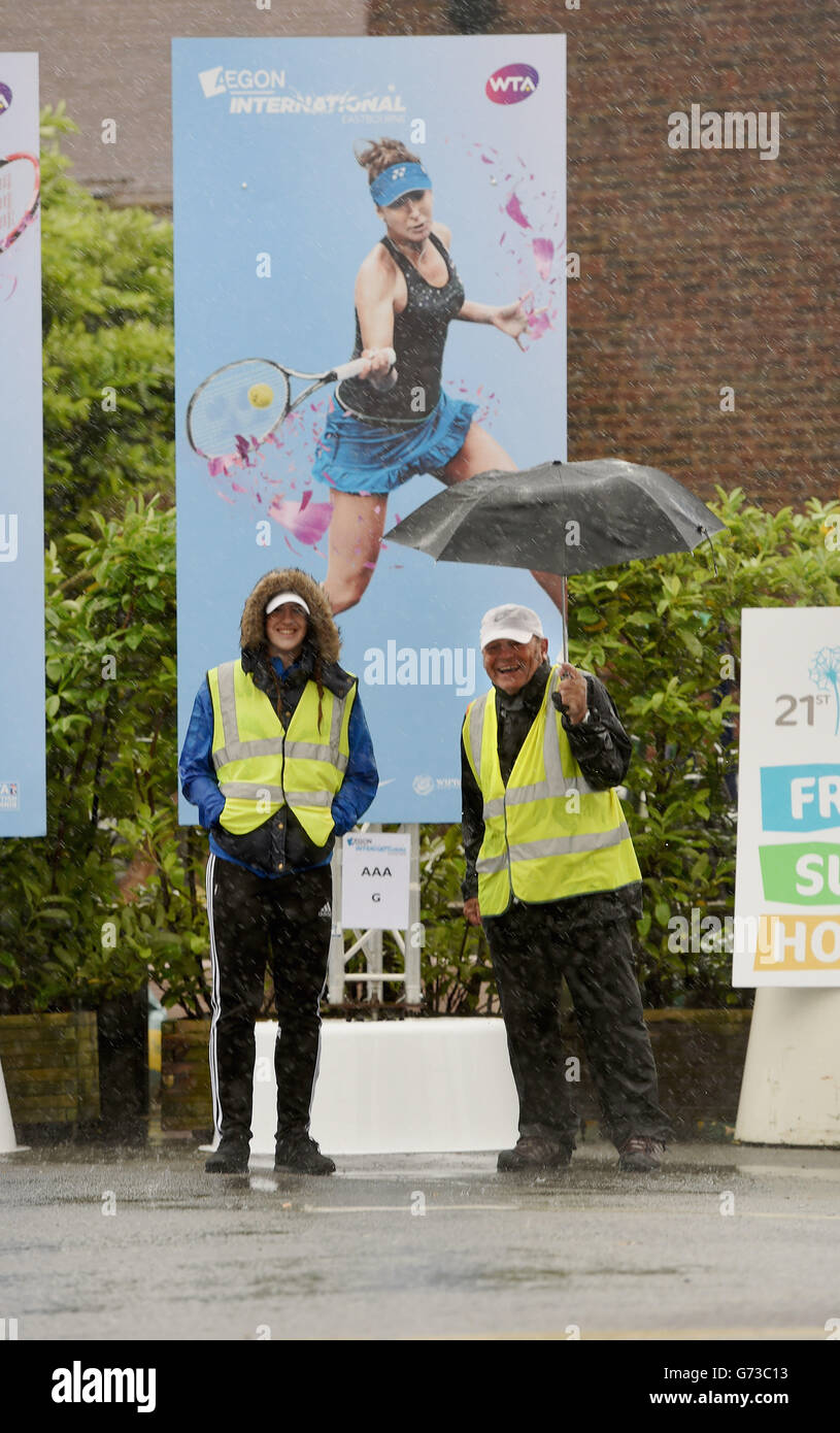 The stewards carry on smiling despite the torrential rain during The Aegon International Tournament at Devonshire Stock Photo
