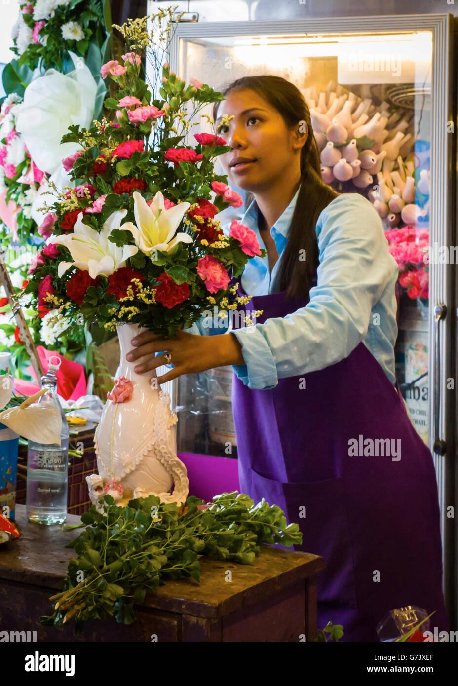 Market florist arranging a bouquet, Thailand. - Stock Image