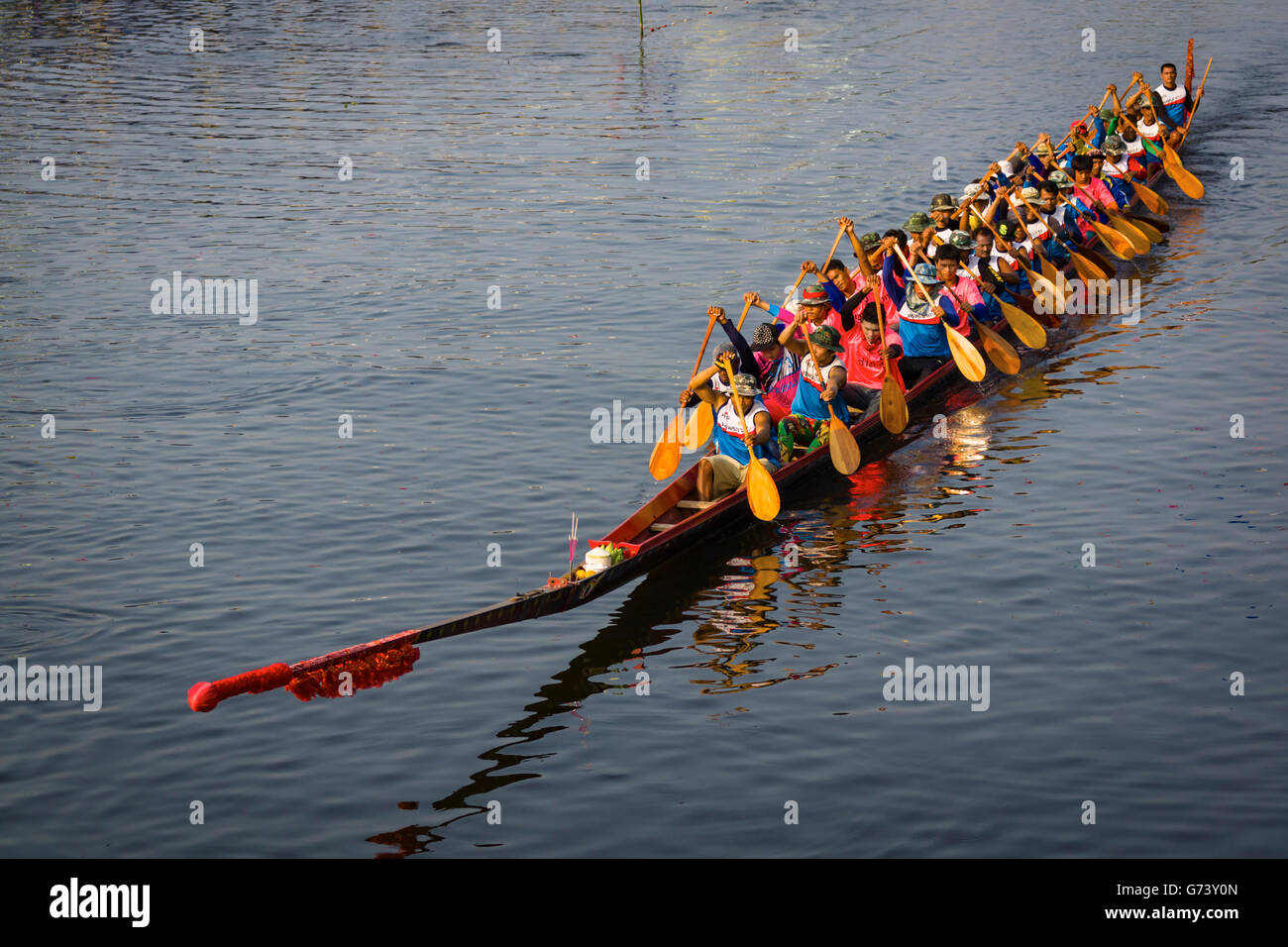 Participants for a longboat racing festival returning to the starting area after completing a race. - Stock Image